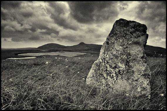 Standing stone with small lochan in the background